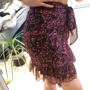 Nederdel med flæser samt bindebælte foran. Elastik i livet bagpå.