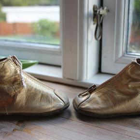Varetype: guld hjemmesko læder læderfutter hjemme sko m. lynlås og gummisåler Farve: guld Oprindelig købspris: 299 kr.  ★ SØDE GULD-LÆDERHJEMMESKO M. LYNLÅS FRA BISGAARD ★  Et par rigtig gode solide hjemmesko i 100% læder i guldfarvet læder. Der er lynlås fortil og ruskindssåler m. gummisål på trædefladerne. Der er god støtte op omkring anklen, og elastik øverst ved anklen så skoene sidder helt til. Snuden er beskyttet af et ekstra stykke læder, så de holder længe.  Størrelsen er en str. 18, og de er fint størrelsesvarende. Indvendigt mål er ca. 10,5 cm.  BEMÆRK IFHT. STANDEN: Min datter har brugt dem, da hun stadig kun kravlede, så den primære slid er på siderne af hjemmeskoene, hvor guldfarven er slidt af flere steder samt på fronten og ved hælene, og på begge snuder ude i den ene side er der et lillebitte hul på ca. 5-6 mm (se billede). Den ene lynlåsdims er faldet af, og der er sat en snor i (se billede). Skoene er på ingen måder udtrådte, da min datter kun har kravlet i dem og måske stået i dem kortvarigt, mens hun har holdt ved sofabordet, men de har jo desværre slid fra kravleriet - deraf den MEGET billige pris ;-) Jeg mener, de dog stadig er gode til at bruge som ekstra hjemmesko, da sliddet ikke er på sålerne, og da gummitrædefladerne stadig ser ud som nye :-)  Skriv emailadresse for billeder i stort format, så du kan zoome ind og se alle detaljerne :-) Nypris kr. 299,-.  ★ FAST PRIS KR. 29,- + B-porto på eget ansvar kr. 14,00 ★  SPAR PORTO og afhent i Esrum, Nordsjælland. Kom også gerne forbi og prøv/se varen ;-)
