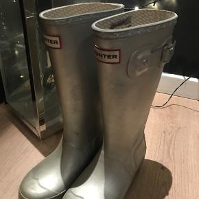 """Sælger disse børne gummistøvler i sølv.  De er brugt. Lugter en smule, men ikke noget man ligger mærke til. Men der følger fine """"sokker"""" med til.  Str. 32  BYD gerne, eller skriv for flere spørgsmål"""