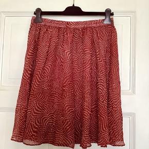 Fin nederdel i 100% silke fra danske Graumann . Farven er rød med hvide prikker. Aldrig brugt , er lidt transparent i silken, så er bedst med en underkjole under. Mål Talje: 38 cm på tværs når elastikken ikke er udstrakt, dvs 76 cm i omkreds når elastikken ikke er udstrakt. Når den er udstrakt måler den 50 cm på tværs, dvs 100 cm i omkreds. Længde: 52 cm. Søgeord: silkenederdel silk skirt silke nederdel rød hvid prikket prikker dots mini midi