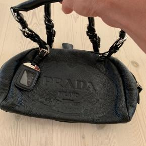 Fantastisk SMUK sort Prada taske med deres flotte velkendte logo, som er præget ind i skindet. Har højst været brugt et par gange!! Købt på Prada Outlet i USA.  Den fremtræder fuldstændig SOM NY, har ingen skrammer, ridser, eller nogen former for brugstegn overhovedet.  Har en rigtig god størrelse, således den både kan bruges til hverdag og samtidig til fest.   Tager ikke imod useriøse henvendelser.  BYTTER IKKE!