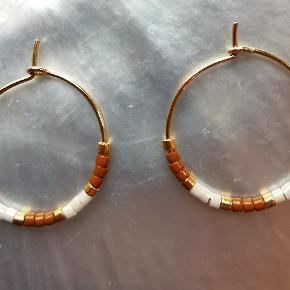 1 par små creoler (20mm) i forgyldt messing med forgyldte Delica Beads, matte gulbrune Delica Beads og shiny creme Delica Beads.   Stand: Helt nye. Jeg laver dem selv.   Bemærk: Prisen er fast.  Skal hentes på Nørrebro (Ravnsborggade) / mødes på Nørreport ellers kommer forsendelse med DAO oveni.   #øreringe #creoler #håndlavet #smykker