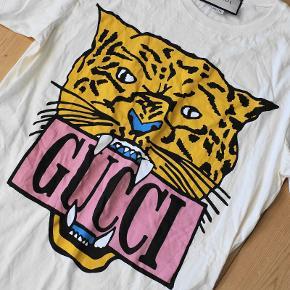 Gucci Oversized T-shirt med Tiger, Beige/Creme Str. M Model / Reference: 492347 XJARG (7136) - Det står på tagget Stand: 10/10 ALDRIG BRUGT! Nypris på €535 i Berlin / knap 4000 kroner Bud modtages gerne Sælges af Gucci som kvinde t-shirt, men vil mene den snildt også kan bruges af herre.  Slå modelnummeret op online for billeder af modellen.  Flere billeder kan sendes på telefon, Instagram, Facebook, snapchat etc. Befinder sig i Aalborg og jeg kører gerne lidt til den rette pris. Er ofte i Århus og skal til KBH i forbindelse med Copenhell. Kan også sendes.  Telefon: 20 23 55 06 Facebook: ralle.knaldsen Instagram: RasmusSkovKjeldsen