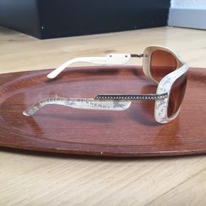 Super cool vintage solbriller fra Burberry fra logo-mania perioden i slut 90'erne og start 00'erne. Der er Burberry logoer på siderne af stellet samt similisten på stængerne. Bundfarven er beige. Glassene er let graduerede. De er købt på loppemarked af en pige der også havde købt dem brugt, så kan ikke være sikker på deres herkomst, men der står stelnr i. De har et par ridser på glassene og skal spændes efter, derfor sælges de billigt. Kom med et bud.   Varen befinder sig i 9520 Skørping. Sender med DAO.  Se også min øvrige annoncer. Jeg sælger tøj, sko og accessories. Pt er min shop fuld af vintagekup, high street fund og mærkevarer i mange forskellige str. Kig forbi og spøg endelig!