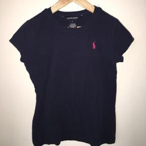 Mørkeblå Ralph Lauren T-shirt til børn med pink logo.   Kan afhentes på Frederiksberg ellers sender jeg med DAO (køber betaler fragt)