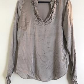 Satin silke skjorte i grå/brun.  Har nogle små udtræk foran, pris sat efter stand.  Materiale: Skjorten har stretch - 95% silke 5% elastan. 🦋  Np: 1499kr.   Mål:  Længde: 65 cm Bryst: Ø104 cm