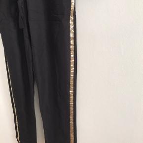 Super lækker buksedragt med guld palietter på siden af buksebenene, lækre sorte glasknapper med guld kant. Bindebånd i taljen