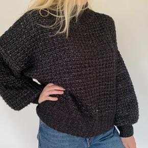 Won Hundred Blakely knit i sort / sølv.  Oversized fit. Puffy sleeves. Turtleneck. 25% wool 44% polyester 31% acrylic.  Lidt nulret og få steder, hvor tråden er gået. Det ser man næsten ikke.