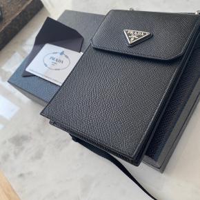 HELT NY - Aldrig brugt. Har kvittering og alt. Lille pung i læder med aftagelig rem. Unisex. Må indse jeg aldrig får den brugt, sælges derfor.  Kan også ses her: https://www.farfetch.com/dk/shopping/men/prada-lille-pung-i-lder-med-aftagelig-rem-item-13533424.aspx