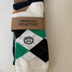 2 pak strømper (et par hvide og et par mørkeblå med ternet mønster på skaft og UO logo) Materiale bomuld med stretch  Str. 40-45 (Kan evt sendes for 20 som brevpost via postnord)