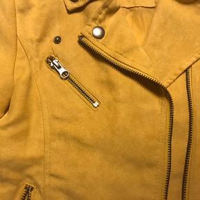 Lækker jakke i imiteret ruskind. Brugt en enkelt gang. Der er en enkelt lille mørk plet på siden af kraven.