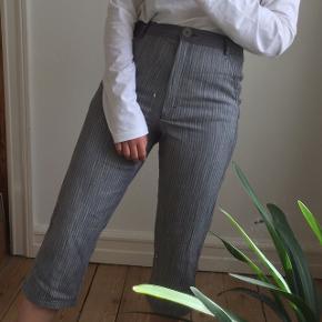 Grå stribede bukser i fin stand. De er højtaljede og passes af en størrelse S.