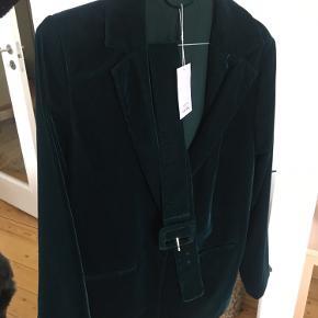 Mellemlang mørkegrøn blazer i velour fra & other stories. Har satin inderfoer i grøn, samt en lille inderlomme. Jakken har et aftageligt bælte i samme stil som jakken, en enkel lukkeknap foran og to forlommer, som er lukkede, men som kan sprættes op. Kan både bruges som overgangs jakke eller bare til at pifte outfittet lidt op med. 💚
