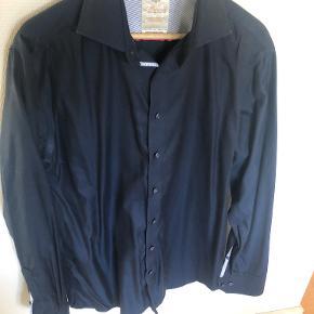 Lækker klassisk skjorte fra Morgan's Goldline linie.  Ny pris: 600 Kvalitet: 100% Bomuld / Stryg let Model: Modern Fit  Bredde: 62cm. (Bryst) Længde: 85cm. (Ned over ryggen) Ærmelængde: 56cm. (fra armhulen og ned til manchetten)