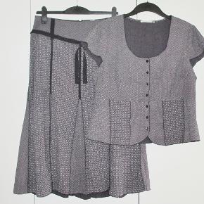 Sæt: Bluse + nederdel med flotte detaljer Størrelse: XL /XXL  2-delt sæt med flotte detaljer. Stoffet er vævet i nuancer i mørk syrenfarvet med sorte detaljer og med sort bælte. Sættet har desuden sort foer. Materialet er 68 % polyester + 32 % viscose. Oprindelig købspris: 1100 kr.  BLUSEN: Brystvidde: 56 cm x 2 Livvidde:     49 cm x 2 Hoftevidde: 59 cm x 2 Længde:      59 cm  NEDERDEL: Livvidde: 43 cm Længde: 79 cm  Ingen byt og prisen er fast