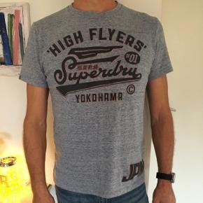 Flot Superdry T-shirt, meleret blågrå med neonorange kanter på teksten. Aldrig brugt, kun prøvet på, da min mand på 50 mener det kun er for mænd på 30🙄😊