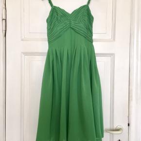 Fin grøn kjole fra H&M . Er købt for en del år siden - i 00' erne - så det er ikke en du umiddelbart vil se se på alle andre når du har den på.  En str 34  Brystmål: 40 cm fra armhule til armhule, dvs 80 cm i omkreds.  Længde: 78 cm målt bagpå uden stropper, stropperne er regulerbare. 98 cm fra stropperne og hele vejen ned, som de sidder i øjeblikket, men kan altså reguleres. Livvidde: ca 33,5 cm på tværs ( dvs 67 cm i omkreds).  I god stand uden huller, fnuller eller lign. Har to små skygger/pletter der dog absolut ikke er meget iøjnefaldende når den er på, da kjolen har så meget vidde i skørtet (se fotos med blyanter).   100% polyester. Kan vaskes i maskinen.   Se også alle mine andre annoncer.  Søgeord: grøn kjole green dress halvtredser stil 50er new look stropkjole midi fest sommer festkjoler sommerkjole 00erne plisseret plisseringer vintage retro