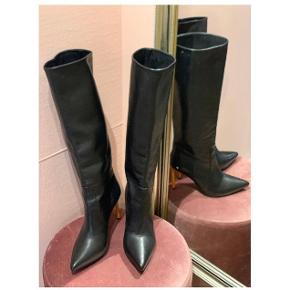 Støvler i sort skind med orange hæle - den ene har et lille mærke.