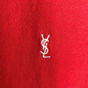 Næsten som ny, klassisk og ikonisk tee fra luksuriøse franske Yves Saint Laurent fra før huset blev omdøbt Saint Laurent Paris.  Købt i butikken i Paris for flere år siden og kostede 1.800kr  Modeller som er ligende denne fra huset nu, koster 2.600kr.