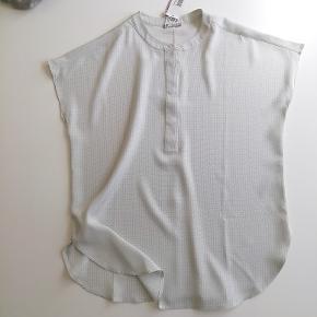 Bytter ikke. Elegant bluse fra Hemisphere str. 36. Skjortebluse med stolpelukning, med skjulte knapper. 100% Silke. Farve: Grå/hvid Bryst mål 2 x 53 cm, for og bag stykket målt ved brystlinjen. Længde fra skulder og ned 64 cm. Købspris kr. 1.999,- Ny. Ubrugt. Kommer fra et ikke ryger hjem. Hænger i dragtpose