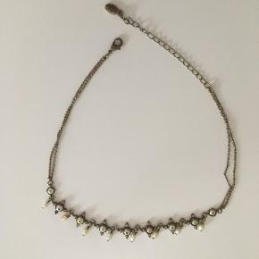 Fin kæde med perler der hænger dekorativt.