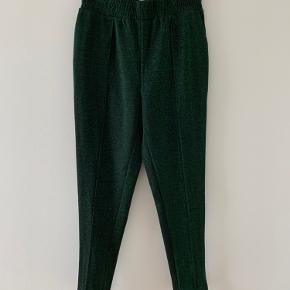 Sælger disse bukser stadig med prismærke i. Det ligner lidt hyggebukser, og sidder derfor ikke stramt. De er grønne med glimmer og så er der en hvid streg i siderne.