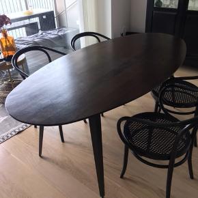 Smukt ovalt spisebord. Fremstillet i mørkt mangotræ med sorte bordben i jern.  Målene på bordet er 200X100. Bordet er købt til 8495 kr. Og er halvanden år gammelt. Brugsspor er en lysere plet på bordet, som det ses på billedet, samt lille ridse.