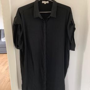 Sort skjortekjole, midi længde (lige over knæet). Brugt meget få gange. Prisen er eks Porto