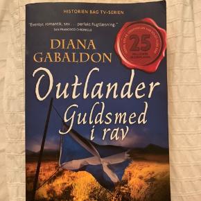 """Sælger bogen """" Outlander, guldsmed i rav"""", skrevet af Diana Gabaldon."""