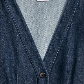 Let figursyet kjole i denim, som går til læggen. Kjolen har V-udskæring med knapper foran og bredt, aftageligt bindebælte.