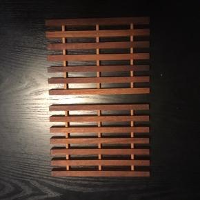 2 fine bordskånere i teaktræ.  Måler 13 x 18 cm.  Sælges samlet for 100 kr.