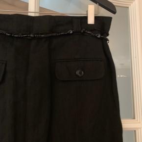 Skøn nederdel med sidelommer og baglommer. Nederdelen har bæltestropper og der medfølger et meget smukt perlebælte. Lukkes med lynlås og en hægte.   Kvalitet: 52% uld, 28% bomuld, 13% polyamide og 7% metal
