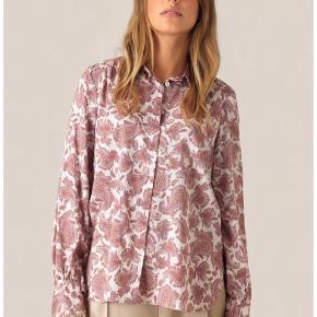 Super fin Hellen Shirt fra Second Female.   Helt ny og stadig med prismærke.   Denne klassiske skjorte er fremstillet i en blød og let 100 % bomuld i et orientalsk inspireret all-over print. Skjorten har klassisk krave, skjult knaplukning og lange ærmer, hvor en manchet med læg, slids og en enkelt knap fuldender looket.  SÆLGES FOR 375 KR PP  BYTTER IKKE!   Kan evt. hentes hos mig på Frederiksberg.