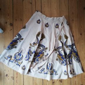 Fin slå-om nederdel med bindebånd og print af drager i blå, hvid og creme. Kan passe alle størrelser da den bindes.