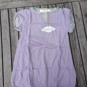Ny sød kjole fra Drappa dot i str. 4 år med  lavendel mønster  Den sødeste kjole med fint lavendelfarvet mønster og fine kanter i andet flot stof. Helt NY. Har fint bælte til salg i anden annonce, der har samme stof som kant. Pris: 50 kr pp