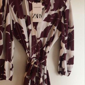 Helt ny fin kjole, med knapper med langs kjolen, og er bånd i taljen. Fine detaljer nederst på kjolen.  Aldrig brugt.