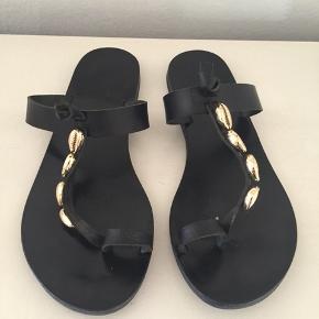 Ancient Greek sandaler i str 38. Brugt minimalt. Sort skind med guld pynt. Æske og dustbag medfølger. Pris 500,- pp Bytter ikke.