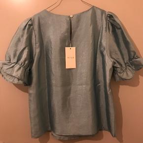 Fin bluse med puffede ærmer og shine-effekt. Aldrig brugt, stadig med prismærke.