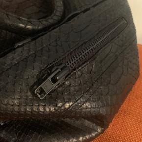 """Slangeskindstaske i rigtig slangeskind. Tasken er stort rum + et mindre rum foran.  Tasken har både en lille hank og en lang skulderrem. Matte YKK lynlåse. Tasken er speciallavet og er derfor en """"éner""""."""