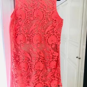 Kjole fra Warehouse, str. 42 med stræk i stoffet. Koralfarvet med extra blondestykke på hele fronten.  Brugt 1 gang så i super fin stand