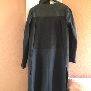 Frakke uden lukning, med fine detaljer. Stoffet giver sig ved ærmerne så den er behagelig at have på