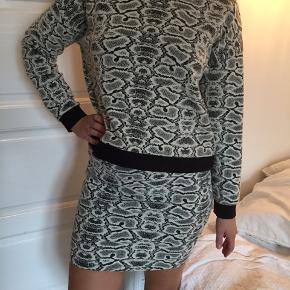 Lækkert todelt sæt. Nederdel og langærmet bluse. Slanskindsmønster. Tekstur i stoffet. Elastisk i stoffet og elastik i linding. Sælges samlet.