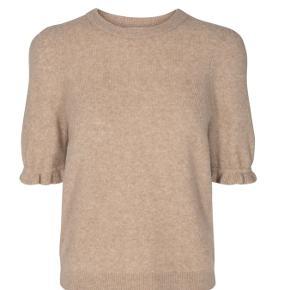Passer str 38-42. Blød og lækker strik t-shirt i skøn uld-blanding. T-shirten har pufærmer med fin flæsekant. Den har rund halsudskæring samt ribkant forneden og i halsen. Den har en løs og afslappet pasform, samt fine detaljer i strikken foran  Style: Lauren SS Puffy Knit