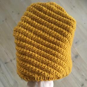 Håndstrikket hue i karry-farve.  100% Uldgarn  Damestørrelse.  Prisen er fast.