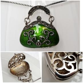 Flot halskæde med emaljeret medaljon udformet som taske i ægte sterlingsølv og med små sten på. Begge dele er stemplet 925. Kæden er 50 cm lang og tasken er 2,4 cm bred og 2,6 cm høj. Fast pris.  Se også mine andre annoncer med smykker 🦋
