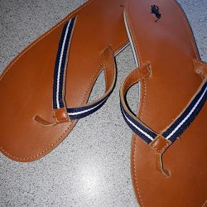 Varetype: sandaler Farve: se foto Prisen angivet er inklusiv forsendelse.  flotte ralph Lauren flip flopper i skind str 39 26 cm indvendig længde  brugt ½ time indendøre men var for store til mig  sælges for 200 kr