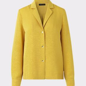 Fantastisk smuk skjorte/ blazer jakke med indvævet guldtråd i det mørke lemon gule stof. Kvalitet: 66% Acetat, 30% Polyester, 4% Metallisk Ærmerne kan foldes op med lille guldknap Skjorten kan anvendes alene men man kan også sagtens have en bluse eller top indenunder og anvende den som blazer/ jakke åben eller lukket  Prisen er fast