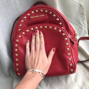 Dette er en super fin rygsæk. Den er fra Michael kors. Den er rød med gulvdetaljer.