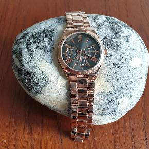 "Rosa ""guld"" ur med koksgrå Metallica urskrive. Måler 18, 5 cm."