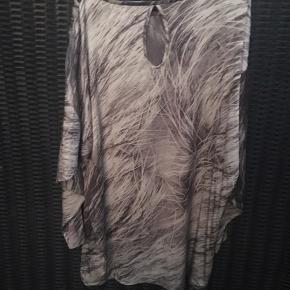 Meget lækker sag i 92% silke + 8% elastan  Dejlig tyngde i stoffet så den falder virkelig fint.  Brugt som overdel der går ned over rumpen, til stramme jeans.  Smart detalje på ryggen.